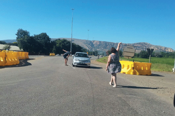 One of the many Samaritans, residents of the R24, assisting to warn oncoming traffic to divert.