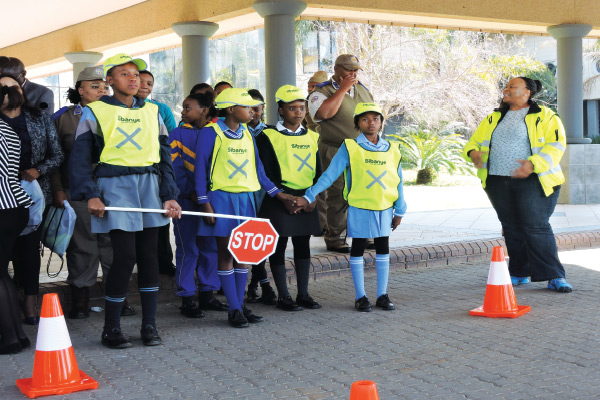 Linda Mekhise, senior road safety officer of the Department of Community Safety and Transport Management (right), practicing proper scholar patrol procedure.